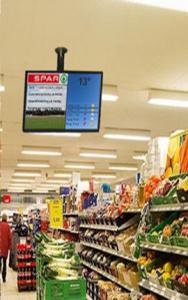 Infoskærm med ½ reklame for en købmand/brugs og ½ information fra lokale foreninger,  her opsat i en købmandsforretning